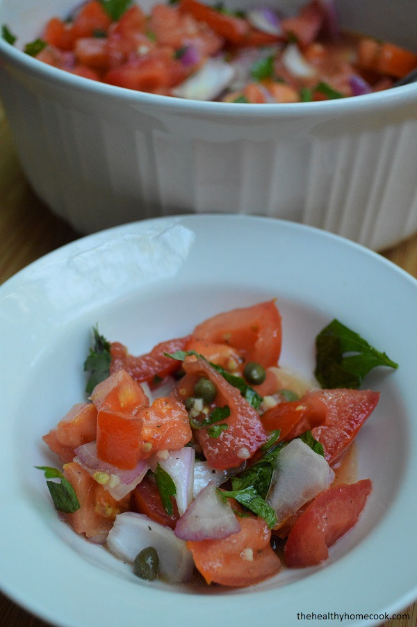 This Tomato Caper salad is bright and packs tons of flavor from fresh herbs, capers, and a light garlic dressing.